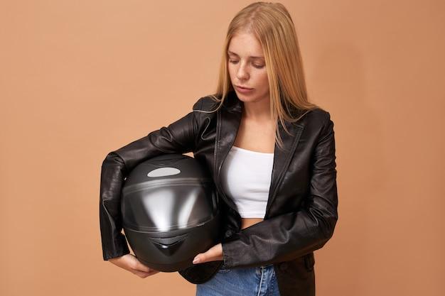 치아 교정기와 긴 스트레이트 헤어 포즈 검은 가죽 재킷에 고립 된 젊은 여성 라이더의 초상화