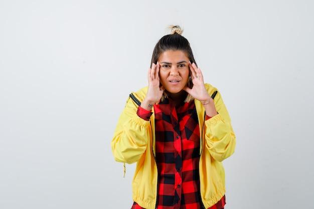 市松模様のシャツ、ジャケット、幸せそうな正面図で寺院をこする若い女性の肖像画