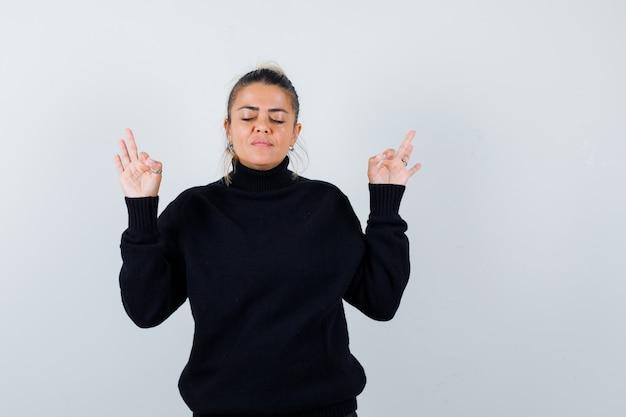 Портрет молодой женщины, демонстрирующей жест медитации в черном свитере с высоким воротом и смотрящей на мирный вид спереди