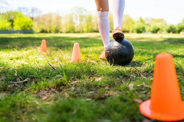 フィールドでボールを練習しながらコーンの周りを走っている若い女性サッカー選手の肖像画。スポーツの概念。