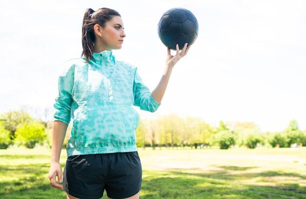 フィールドに立って、サッカーボールを保持している若い女性サッカー選手の肖像画。スポーツのコンセプト。