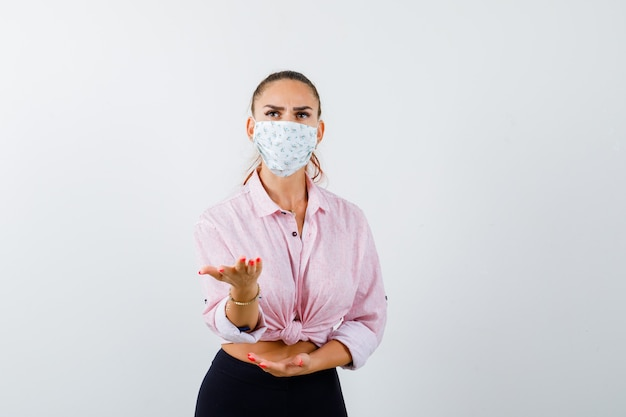 Портрет молодой женщины, протягивающей руку в озадаченном жесте в рубашке, брюках, маске и выглядящей сердитым видом спереди