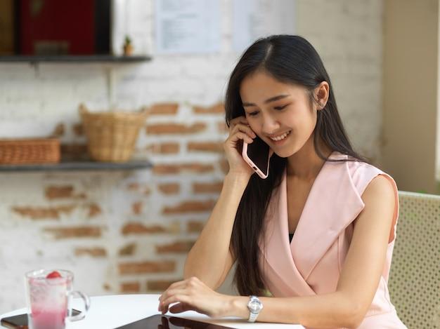 カフェのコーヒーテーブルに座って電話で話している若い女性の肖像画