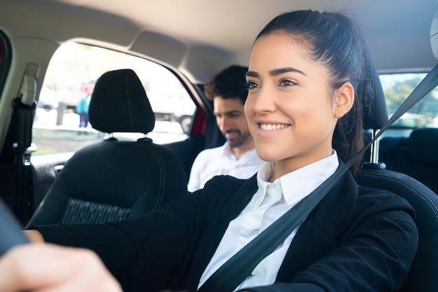 뒷좌석에 사업가 승객이 있는 젊은 여성 택시 운전사의 초상화
