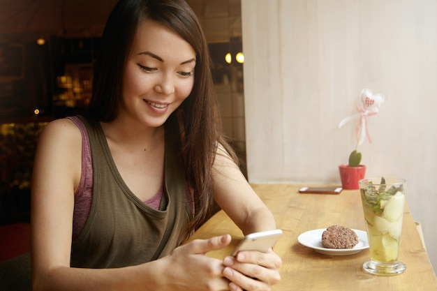 Портрет молодой женщины с волосами брюнетки с помощью телефона