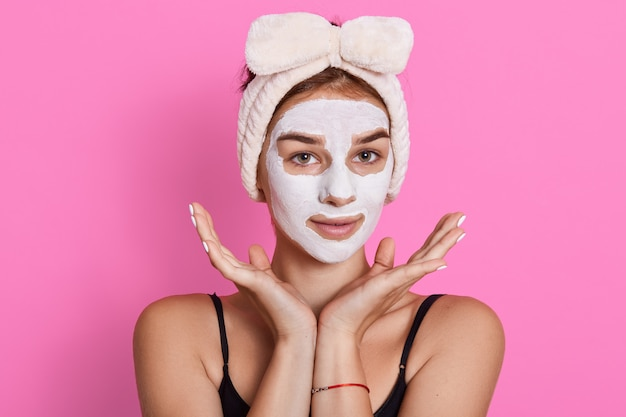 顔の粘土マスクを持つ若い女性の肖像画は、頭の周りに白いヘアバンドを持っています