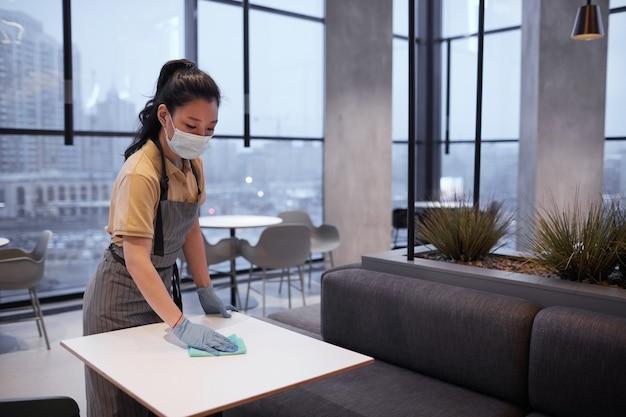 レストランやフードコートのインテリア、コピースペースでテーブルを掃除しながらマスクを身に着けている若い女性労働者の肖像画