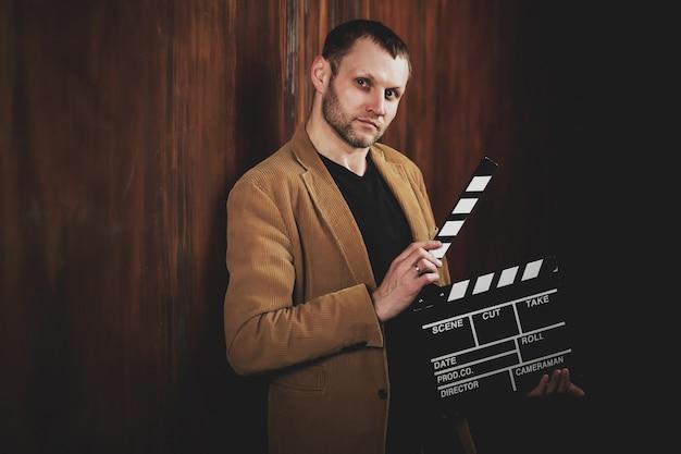 Kinopremiereの映画クラッカーと若い映画監督の肖像画。映画サービスの分野のビジネスマンは、映画を提示します。あなたの仕事への真剣なアプローチと結果への自信の概念。コピースペース