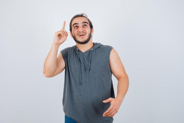 Портрет молодого подтянутого мужчины, указывая вверх, предлагая рукопожатие в качестве приветствия в толстовке без рукавов и веселый вид спереди