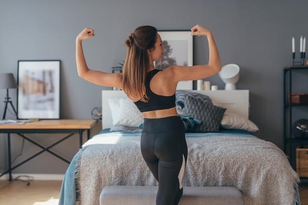 근육을 보여주는 젊은 피트 니스 여자의 초상화