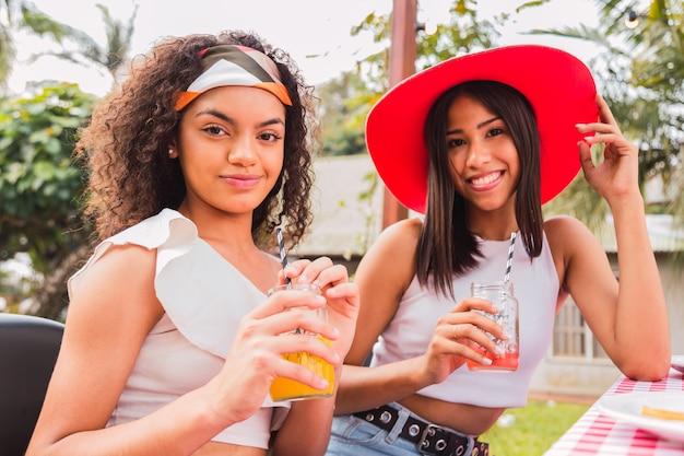 ジュースを飲む若い友人の肖像画。夏の日を楽しんでいる2人のブルネットの友人。夏と友情の概念。