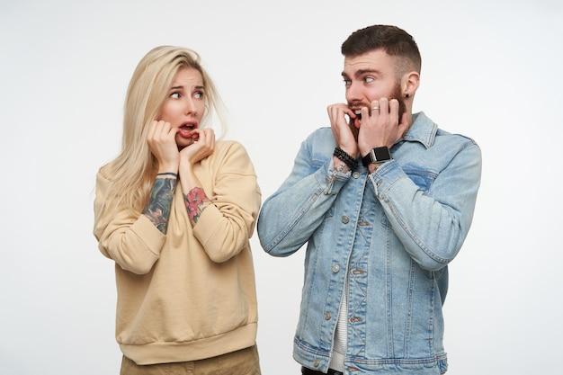 彼らの顔に上げられた手を保持し、白でポーズをとって、口を開けてお互いを怖がって見ている若いおびえたカップルの肖像画