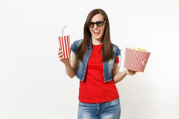 흰색 배경에 격리된 팝콘 양동이와 플라스틱 컵의 소다 또는 콜라를 들고 영화를 보고 있는 3d 안경을 쓴 젊고 매력적인 브루네트 여성의 초상화. 영화 개념의 감정.