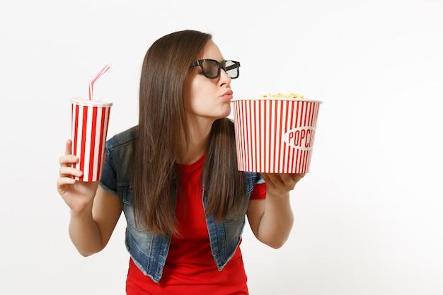 흰색 배경에 격리된 팝콘 양동이와 플라스틱 컵의 소다 또는 콜라를 들고 영화를 보고 있는 3d 안경을 쓴 젊고 매력적인 여성의 초상화. 영화 개념의 감정.