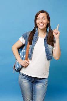 Портрет молодого смешного красивого студента женщины в джинсовой одежде с рюкзаком указывая указательный палец вверх смотрящ в сторону изолированный на голубой предпосылке. обучение в колледже. скопируйте место для рекламы.