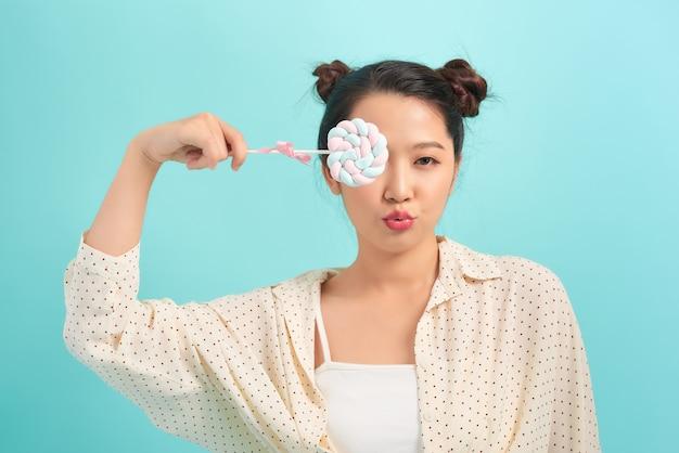 Портрет молодой смешной модной девушки позирует на синей стене
