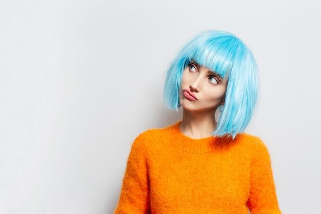 흰 벽에 주황색 스웨터를 입고 파란 머리를 가진 젊은 재미있는 여자의 초상화.
