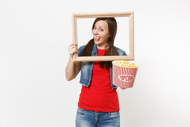 캐주얼 옷을 입고 영화를 보고 팝콘과 액자를 들고 흰색 배경에 고립 된 혀를 보여주는 젊은 재미 있는 예쁜 여자의 초상화. 영화 개념의 감정.