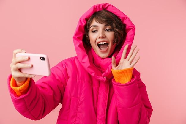 Портрет молодой смешной женщины в теплом пальто, делающей видеозвонок и махающей рукой, изолированной на розовом