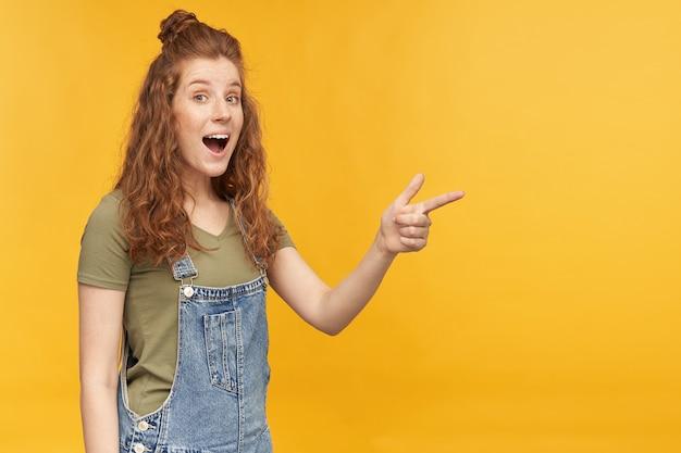 ウェーブのかかった長い髪の若い生姜の女性の肖像画は、驚いた、ショックを受けた表情でコピースペースに指で示しています。黄色の壁に隔離