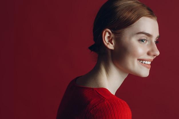 Портрет молодой рыжей улыбки женский портрет профиля на красном фоне