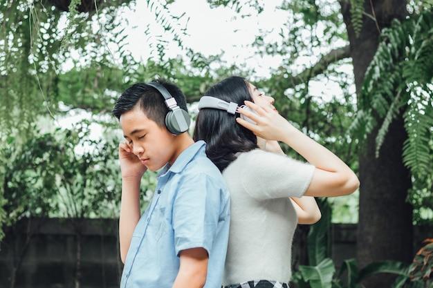 Портрет молодой девушки и мальчика слушать музыку с помощью наушников