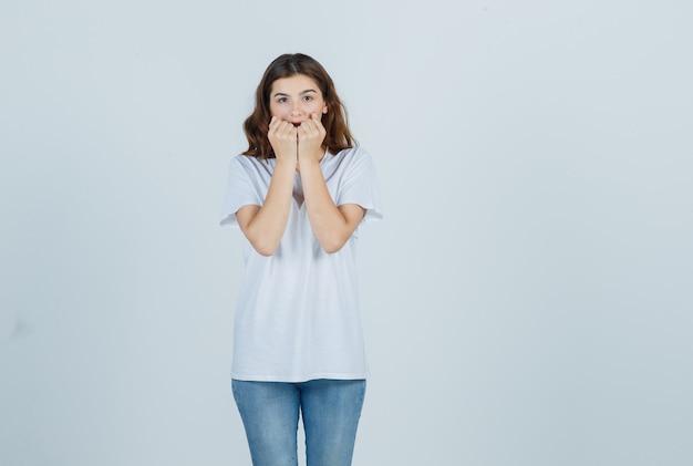 Портрет молодой девушки эмоционально кусает кулаки в белой футболке и испуганно смотрит спереди
