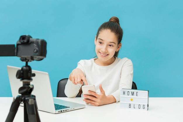 Портрет молодой девушки, снимающий для личного блога