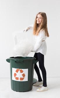 プラスチックをリサイクルして幸せな若い女の子の肖像画