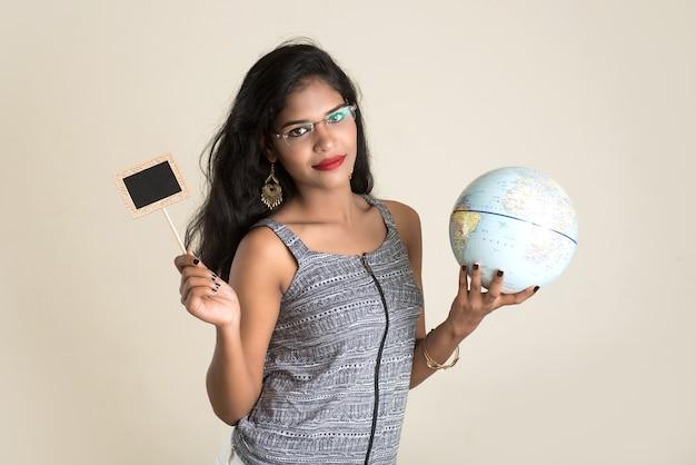Портрет молодой девушки, держащей и позирующей с глобусом мира и небольшой черной доской