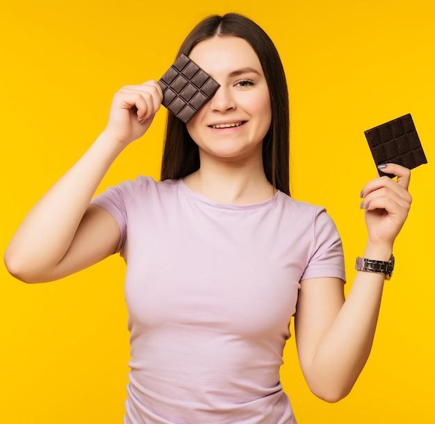 Портрет молодой девушки, держащей плитку шоколада на ее лице