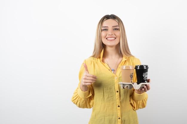 Портрет молодой девушки держа чашки кофе и давая большие пальцы руки вверх.
