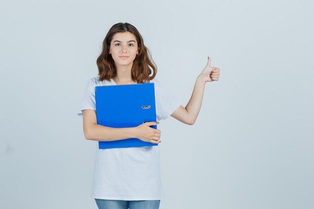 Портрет молодой девушки, держащей папку, показывая большой палец вверх в белой футболке и весело смотрящей спереди
