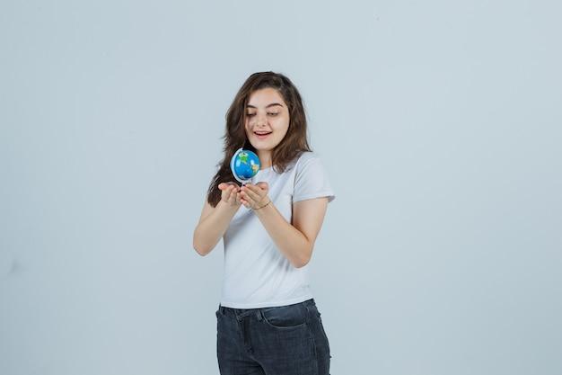 Портрет молодой девушки, держащей глобус в футболке, джинсах и выглядящей изумленно вид спереди