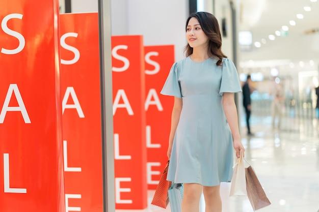 ショッピングモールを歩いて買い物袋を持っている若い女の子の肖像画