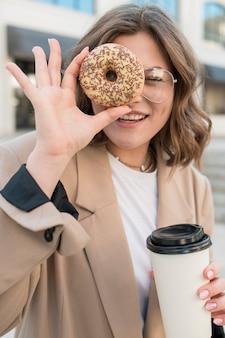Портрет молодой девушки, холдинг вкусный пончик