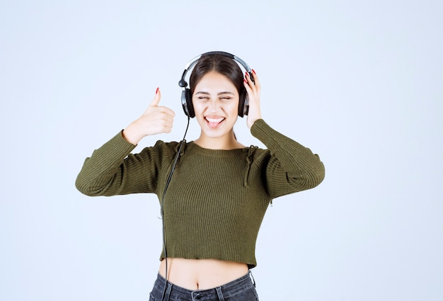 Портрет молодой девушки в наушниках, слушать музыку и давать большие пальцы руки.