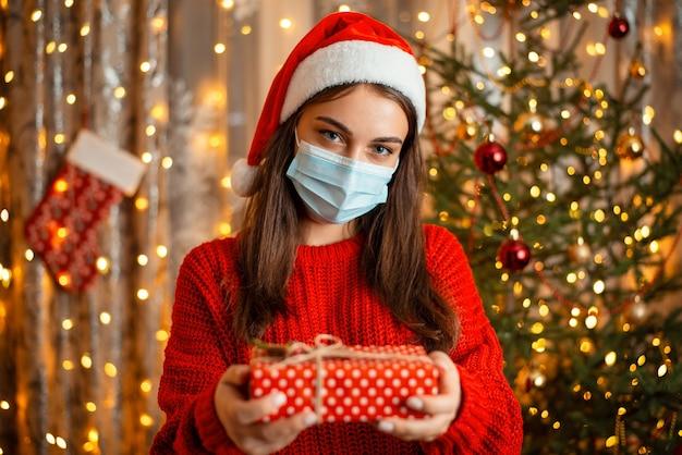 プレゼントとクリスマスツリーの前に立っている医療マスクとサンタ帽子の少女の肖像画