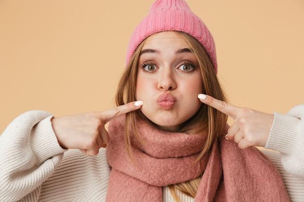 Портрет молодой девушки в зимней шапке, затаив дыхание, изолирован на бежевом