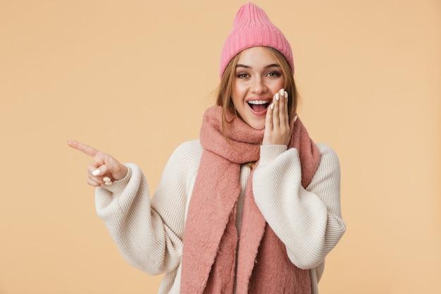 Портрет молодой девушки в зимней шапке, улыбаясь и указывая пальцем в сторону на copyspace, изолированные на бежевом