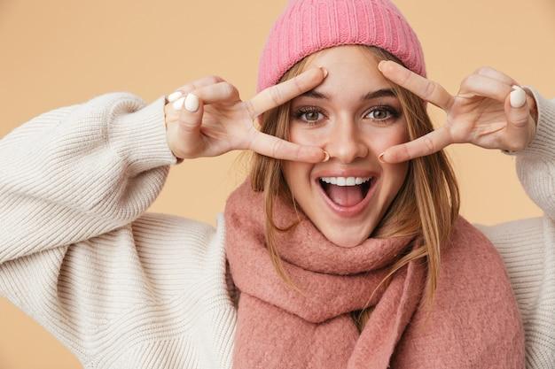 Портрет молодой девушки в зимней шапке, улыбаясь и показывая пальцы мира, изолированные на бежевом