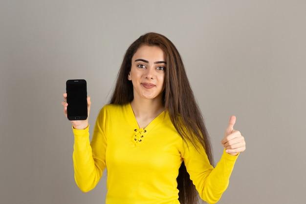 Портрет молодой девушки в желтом холдинге сотовый телефон на серой стене.
