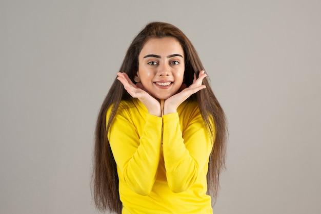 Портрет молодой девушки в желтом топе смотрит и улыбается на серой стене.