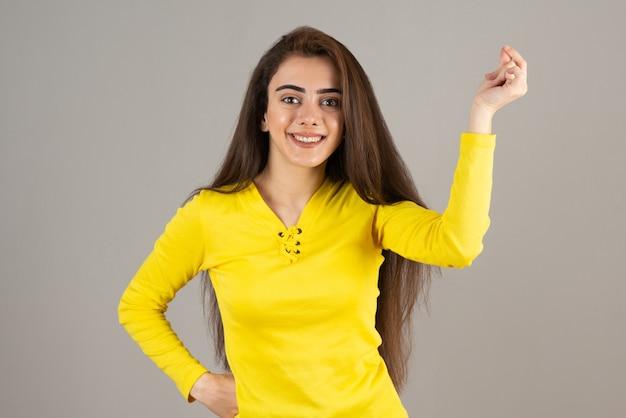 회색 벽에 노란색 상단 서 있는 어린 소녀의 초상화.