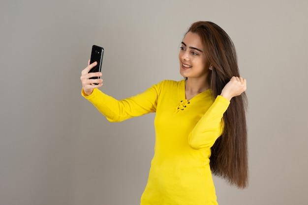 Портрет молодой девушки в желтом топе, делающей селфи через мобильный телефон на серой стене.