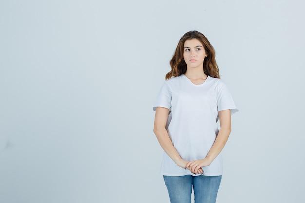 Портрет молодой девушки, держащей руки перед собой в белой футболке и задумчивой смотрящей спереди