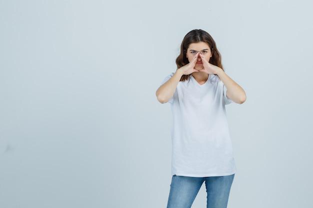 Портрет молодой девушки, держащей руки, чтобы рассказать секрет в белой футболке, джинсах и серьезного вида спереди