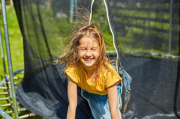 Портрет молодой девушки на батуте на открытом воздухе, на заднем дворе дома в солнечный летний день, летние каникулы, счастливый маленький ребенок прыгает на батуте
