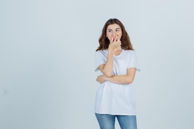 흰색 티셔츠, 청바지에 입술을 꼬집고 사려 깊은 전면보기를 찾고 어린 소녀의 초상화
