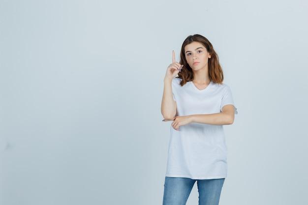 Портрет молодой девушки, указывающей вверх в белой футболке и выглядящей разумно, вид спереди